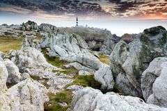 Unreal rocky coastline. At dusk in the Ouessant island with the Creach lightohuse, Brittany, France Royalty Free Stock Photography