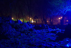 Unreal rainy evening park scene. Surreal view of rainy evening in the Seaside Park ,mysterious shadows,trees silhouettes ghostly blue illuminated rocks shapes Royalty Free Stock Photo