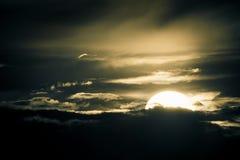 Unreal sky. Mystical night scene. Glowing sun bathing in a dark dramatic sky Stock Photos