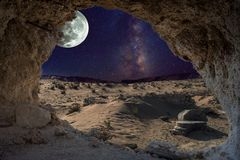 An unrealistic night landscape through a cave with milky, moon in eclipse, and desert with ruins of ancient columns. Royalty Free Stock Image