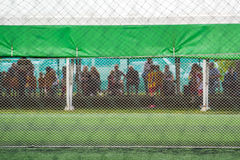 Unrecgonizable audience watching kids soccer game. Unrecgonizable audience watching kids playing soccer game Stock Photo
