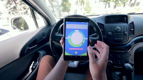 Unrecignizable man plays Pokemon Go in a car. stock video footage