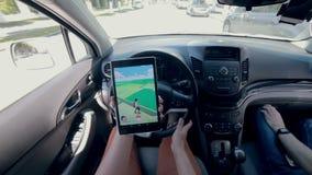 Unrecignizable man plays Pokemon Go in a car. stock footage