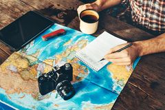 Unrecognazable Traveler Man Is Planning Vacation Travel With Map. He Drinks Coffee And Marks royalty free stock images