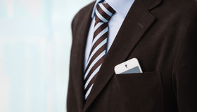 Unrecognisable confident business man wearing suit. Closeup of torso of confident business man wearing elegant suit and mobile phone at pocket Royalty Free Stock Photography