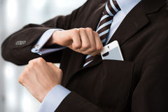 Unrecognisable confident business man wearing suit. Closeup of torso of confident business man wearing elegant suit taking mobile phone from pocket Stock Images