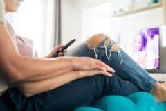 Unrecognisable het houden van paar het letten op televisie bij hun modern huis De holdingsafstandsbediening van de vrouw stock fotografie