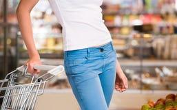 Unrecognisable het vrouwelijke winkelen bij supermarkt met karretje royalty-vrije stock fotografie