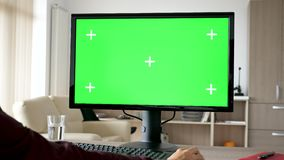 Unrecognisable man typing on personal computer keyboard with big green screen chroma mock-up. In the living room of his house. Dolly slider 4K footage with stock video