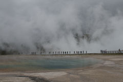 Unrecognisable people walking by Midway Geyser Basin through steam Royalty Free Stock Image