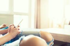 unrecognisable vrouwenzitting op bank het ontspannen bij haar modern huis Vrouw die mobiele telefoon houden, die het Web doorblad royalty-vrije stock afbeelding
