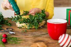 Unrecognisable woman making christmas wreath in living room. DIY Christmas decoration concept. Hands close up. royalty free stock photos