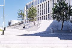 Unrecognisable young woman on the white steps of a new college building. A small figure of an unrecognisable young woman sitting on the steps of new City of Royalty Free Stock Photos