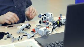 Unrecognised ребенок смотря детали ` s робота Конец-вверх 4K сток-видео