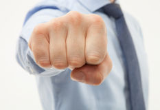 Unrecognizabl businessman showing a stronge fist. Unrecognizable businessman showing a strong fist, white background Royalty Free Stock Images