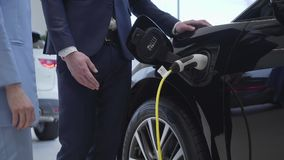 Unrecognizable επαγγελματικός πωλητής στο κοστούμι που στέκεται κοντά στη χρέωση του ηλεκτρικού αυτοκινήτου που εξηγεί τα πλεονεκ απόθεμα βίντεο