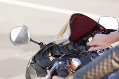 Unrecognizable żeński rowerzysta obraca dalej silnika motocykl, utrzymanie ręka na kluczu, przygotowywającym jechać przeciw asfal zdjęcia stock