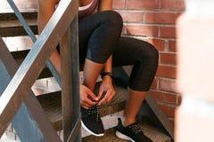 Unrecognizable δένοντας δαντέλλες γυναικών των αθλητικών παπουτσιών Στοκ Φωτογραφίες