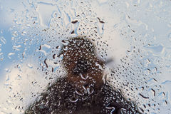 Unrecognizable αντανάκλαση σκιαγραφιών ατόμων σε ένα υγρό παράθυρο στοκ εικόνες