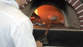 Unrecognizable αρσενικός Baker παίρνει από το ψωμί στην ξύλινη καίγοντας σόμπα για το ψήσιμο Ο αρχιμάγειρας ψήνει Flatbread Pita  φιλμ μικρού μήκους