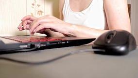 Unrecognizable γυναίκα χρησιμοποιώντας ένα ποντίκι και δακτυλογραφώντας κάτι στο πληκτρολόγιο lap-top, ρηχή εστίαση απόθεμα βίντεο