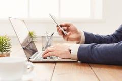Unrecognizable επιχειρηματίας που χρησιμοποιεί το lap-top και το τηλέφωνο Στοκ φωτογραφία με δικαίωμα ελεύθερης χρήσης
