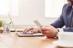 Unrecognizable επιχειρηματίας που χρησιμοποιεί το lap-top και το τηλέφωνο Στοκ Φωτογραφίες