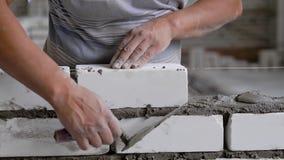 Unrecognizable εργαζόμενος συγκομιδών που βάζει τα τούβλα εργαζόμενος στο εργοτάξιο οικοδομής φιλμ μικρού μήκους