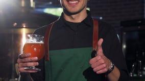 Unrecognizable ζυθοποιός στην ποδιά που παρουσιάζει αντίχειρες, που κρατούν το ποτήρι της μπύρας φιλμ μικρού μήκους