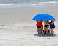 Unrecognizable κυρίες που λαλιούνται κάτω από μια ομπρέλα παραλιών που προσπαθεί να πάρει από τον καυτό θερινό ήλιο σε μια παραλί στοκ εικόνες
