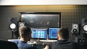 Unrecognizable νέοι αρσενικοί ακουστικοί συντάκτης και παραγωγός μουσικής που εργάζονται στο στούντιο καταγραφής Υγιής δημιουργία φιλμ μικρού μήκους