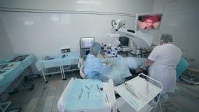 Unrecognizable ομάδα γιατρών που εκτελεί τη χειρουργική επέμβαση στο λειτουργούν δωμάτιο νοσοκομείων φιλμ μικρού μήκους