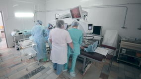 Unrecognizable ομάδα γιατρών που εκτελεί τη χειρουργική επέμβαση στο λειτουργούν δωμάτιο νοσοκομείων απόθεμα βίντεο