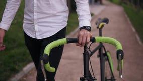 Unrecognizable σκεπτικός νέος επιχειρηματίας που περπατά με το ποδήλατο στην οδό στην πόλη Κύλισμα του ποδηλάτου οδοιπορίας του ε φιλμ μικρού μήκους