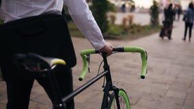 Unrecognizable σκεπτικός νέος επιχειρηματίας που περπατά με το ποδήλατο στην οδό στην πόλη Κύλισμα του ποδηλάτου οδοιπορίας του ε απόθεμα βίντεο