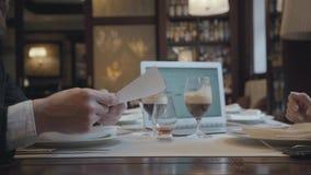 Unrecognizable συνεδρίαση ανδρών και γυναικών στον πίνακα στην εργασία καφέδων Το lap-top, τα έγγραφα και τα γυαλιά με τον καφέ ε φιλμ μικρού μήκους