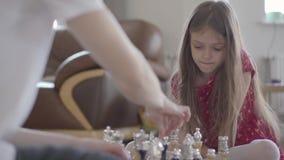 Unrecognizable συνεδρίαση σκακιού πατέρων και μικρών κοριτσιών παίζοντας στο πάτωμα κοντά επάνω Η κόρη κερδίζει, είναι συγκινημέν απόθεμα βίντεο