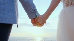 Unrecognizable χέρια εκμετάλλευσης γαμήλιων ζευγών στο υπόβαθρο ηλιοβασιλέματος ή ανατολής Νύφη και νεόνυμφος που στέκονται την υ φιλμ μικρού μήκους