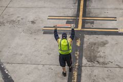 Unrecognizable airport worker gets ready to guide an airplne in to land with red flasher sticks royalty free stock image