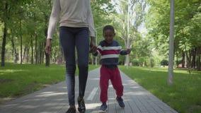 Unrecognizable amerykanin afryka?skiego pochodzenia kobiety odprowadzenie w parku z jej ma?ym synem, mienie r?ki ?liczny dziecko  zdjęcie wideo
