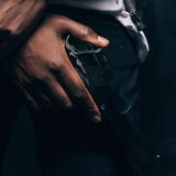 Unrecognizable armed black criminal man closeup. Studio shoot. Gangster guy with gun in hand on dark background. Outlaw, ghetto, murderer, robbery concept Royalty Free Stock Image