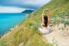 Unrecognizable athletic woman 25-30 sitting on the hill in bra and pants. Doing yoga. royalty free stock photo