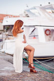 Unrecognizable attractive redheaded girl in white summer dress. Sits by the berth with yachts background. Sea rest concept Stock Photo
