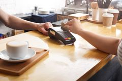 Unrecognizable barman taking payment from client at counter of a coffee shop. Unrecognizable barman giving POS terminal to customer with credit card at coffee Stock Image