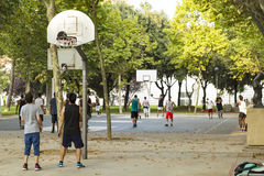 Unrecognizable basketball players on numerous courts on a nice sunny day in a park Royalty Free Stock Images