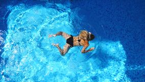 Unrecognizable beautiful girl in black swimsuit swimming across pool of luxury hotel. Young woman relaxing in warm water stock video