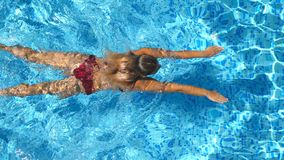 Unrecognizable beautiful girl in red bikini floating across the pool of hotel. Young woman swimming in clear blue water. Of basin on sunny day. Concept of stock video footage