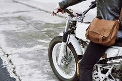 In Search of Adventure. Unrecognizable biker wearing jeans and leather jacket riding vintage motorcycle in search of adventure Stock Images