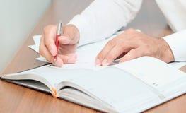Unrecognizable biznesmen bierze notatki w nabiale, obrazy stock