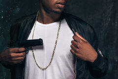 Unrecognizable black man threatens with a gun. Closeup studio shoot. Ghetto gangster with weapon on dark background. Outlaw, ghetto, murderer, robbery concept Stock Image